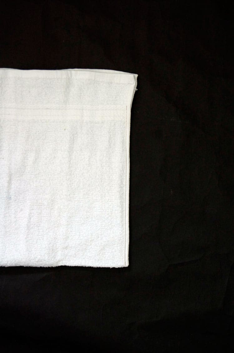Edges of white terrycloth towel sewn together to form bag.