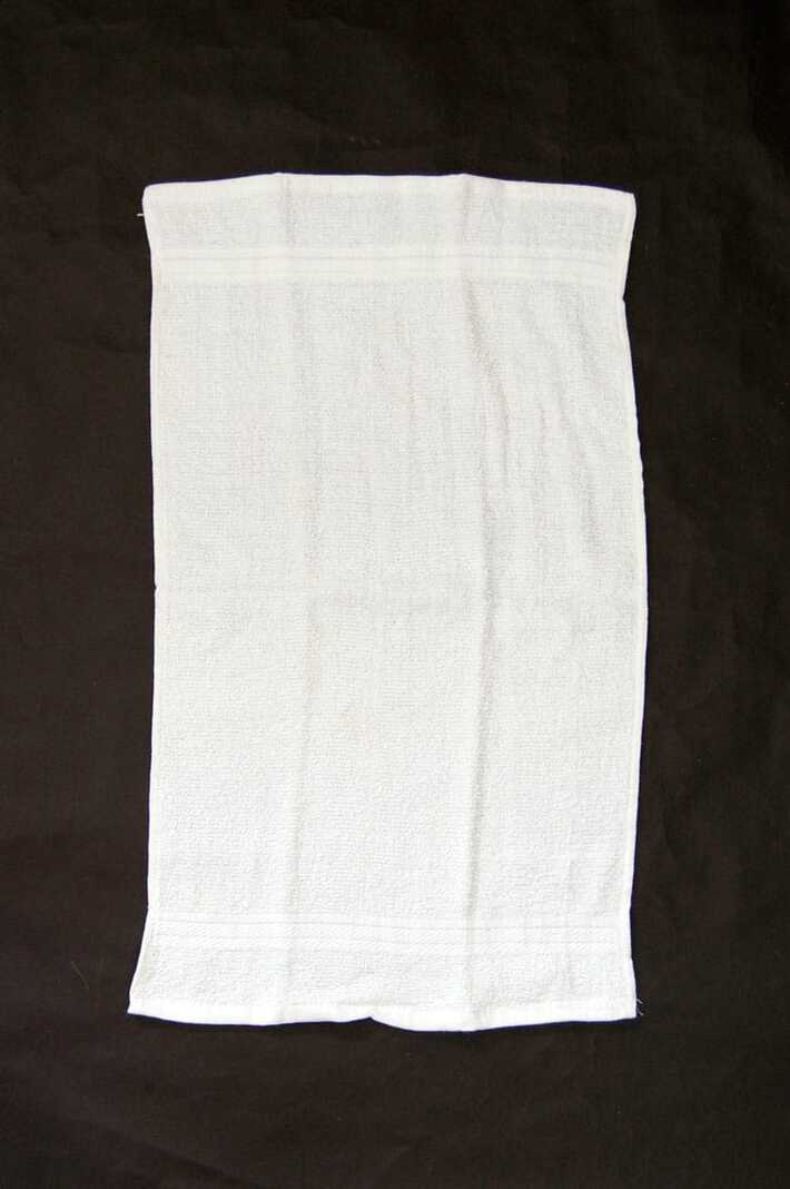 Inexpensive white terrycloth hand towel laid on a black table.