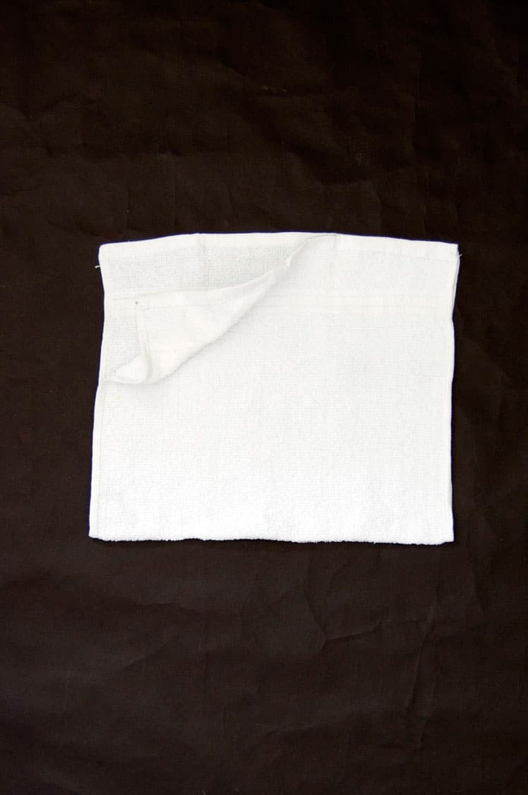 Hand towel folded in half to make a square.