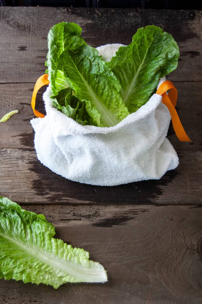 Bright green romaine lettuce sticking out of a white terry towel salad bag on a wood table.