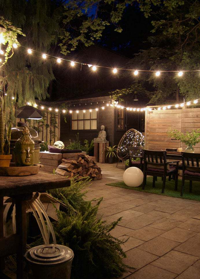 Courtyard backyard with square cut flagstone and a variety of innovative lighting.