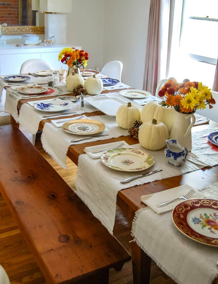 Harvest table set for Thanksgiving with white foam pumpkins and jugs of orange, red and yellow mums.