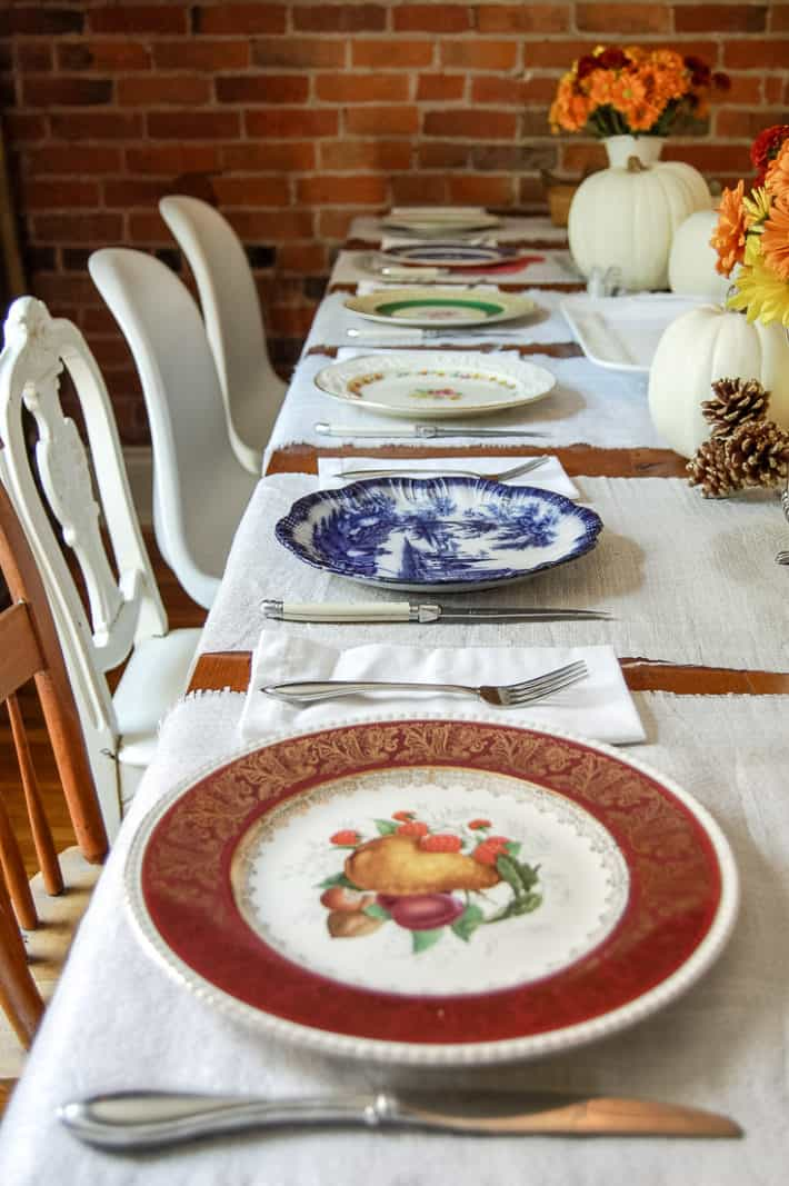 Mismatched antique plates set for a Thanksgiving table.
