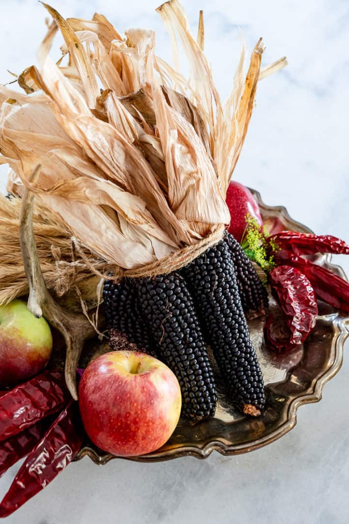 A fall harvest centerpiece with black corn, apples and dried peppers on a tarnished silver platter.