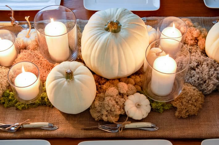Moss and pumpkin table scape seen from above with clear vases filled with white candles throughout.