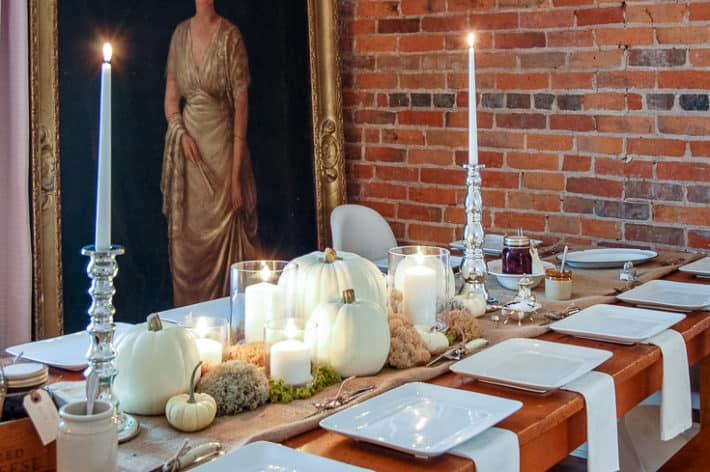 Table set with a table scape of mercury glass candlesticks, white pumpkins, and preserved moss.