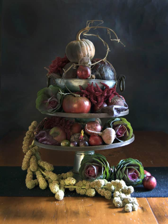 A Thanksgiving centerpiece tower of fall vegetables and grains.