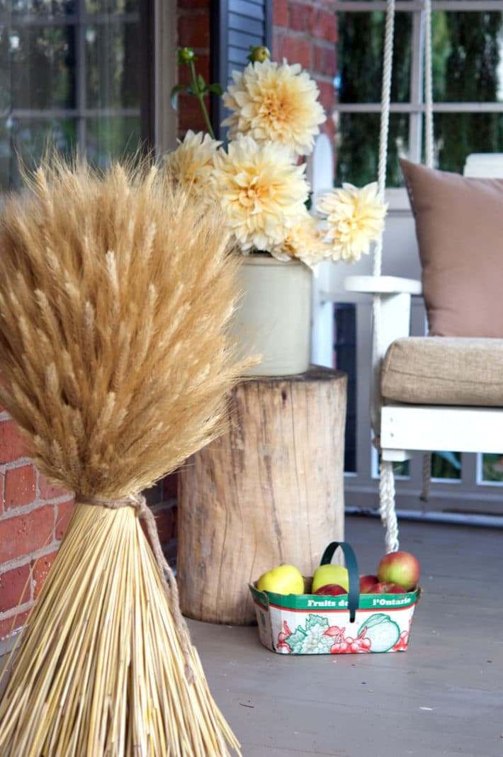 Fall porch decorated with a huge wheat sheaf, pale peach dahlias in an antique crock and a basket of apples.