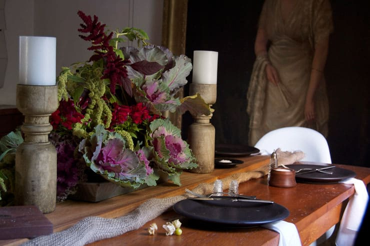 A moody Thanksgiving table with big rustic wood candleholders flanking an arrangement or red and green amaranth and ornamental cabbage.