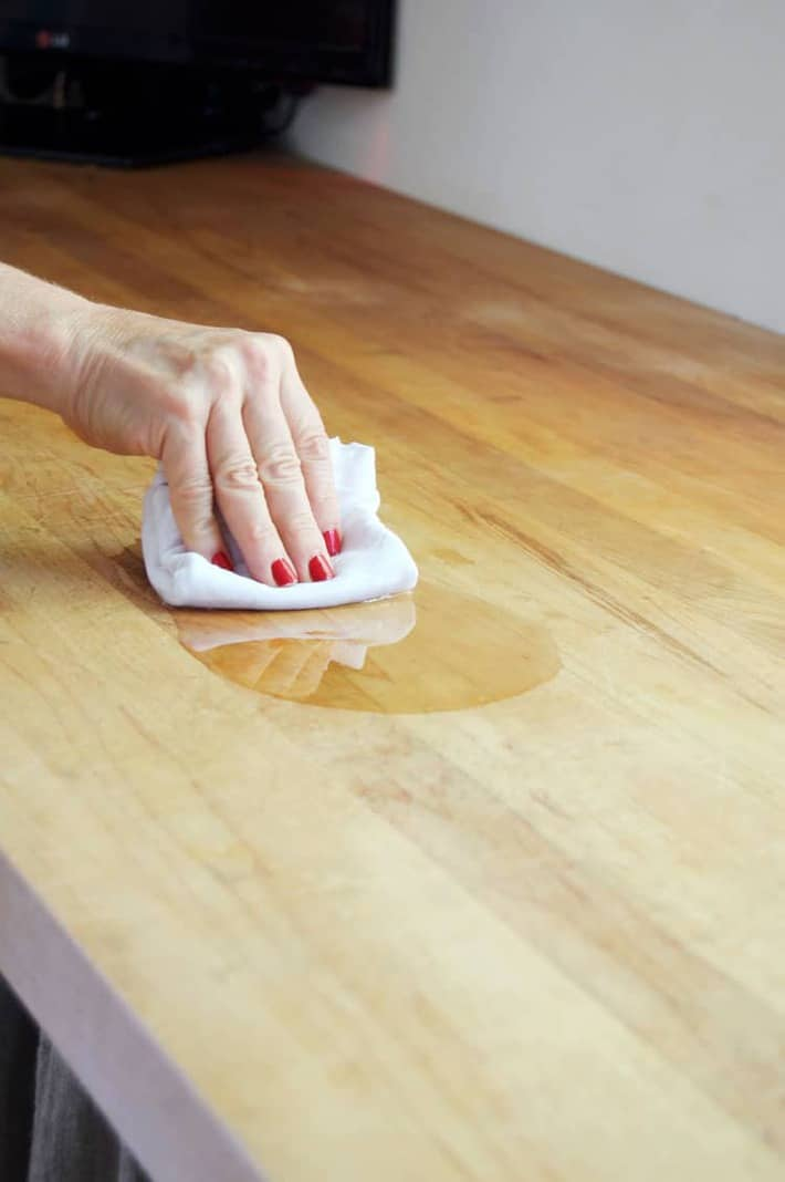 Wiping mineral oil into a wood counter to condition it.