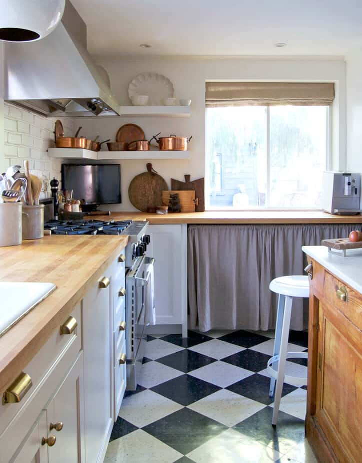 Modern country kitchen with black and white check floors, white shaker cabinets and a ruffled curtain under counter.