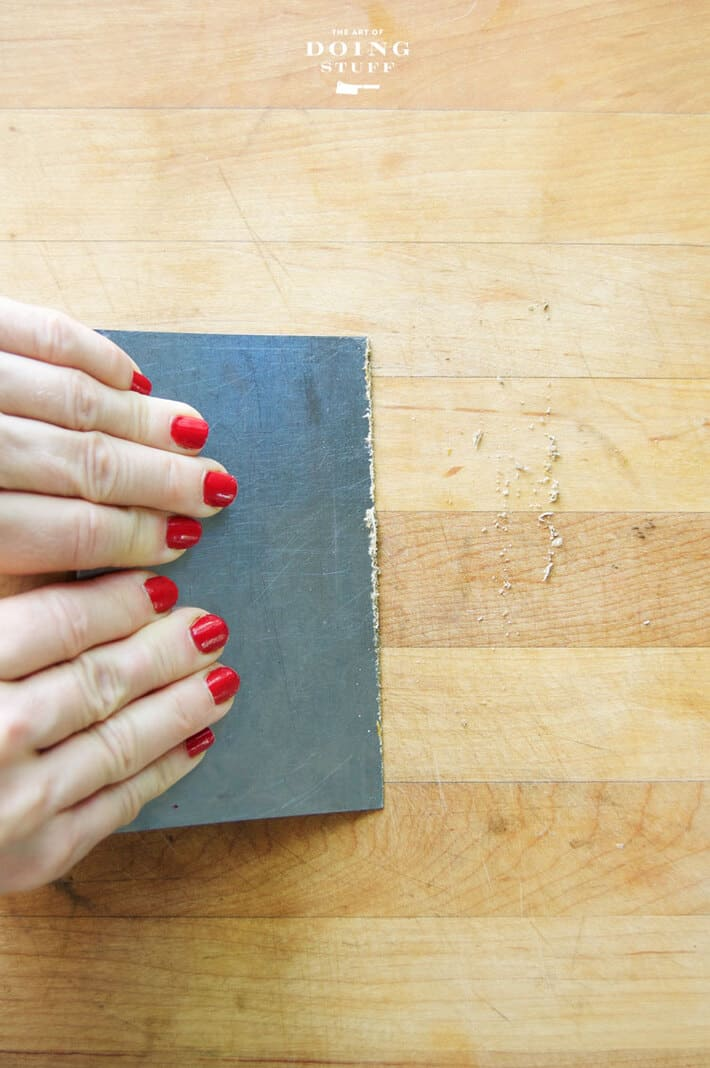Woman's hands with red nailpolish run a dough scraper across a wood counter to remove guck.