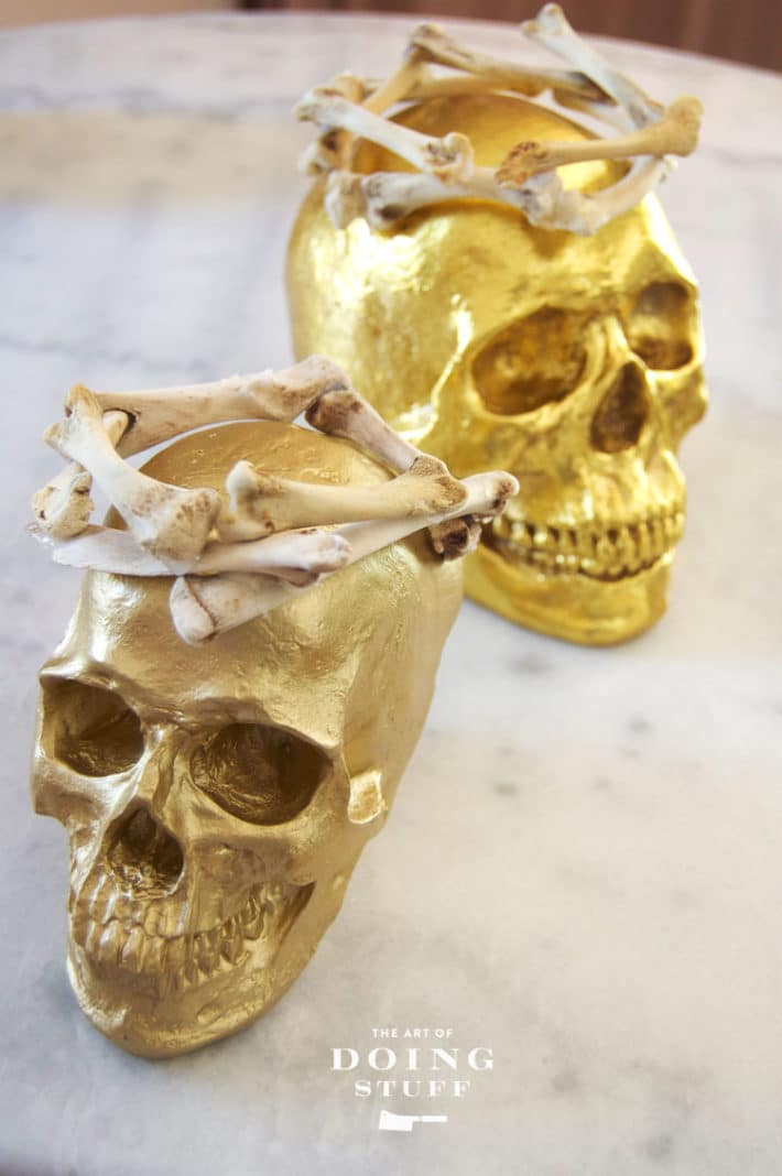 Weirdly elegant Halloween decorations of gold skulls with crowns on marble table.