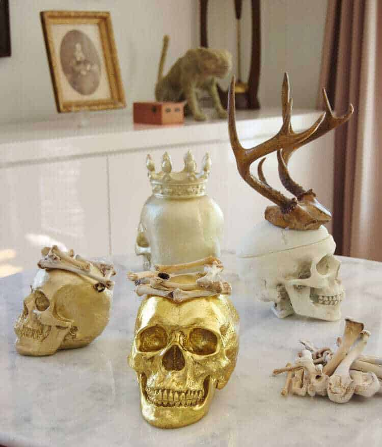 Several skulls displayed on marble table with white lacquer buffet in background.