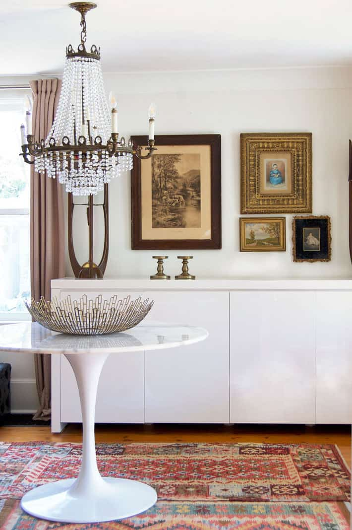 Empire chandelier with gallery wall and tulip table.