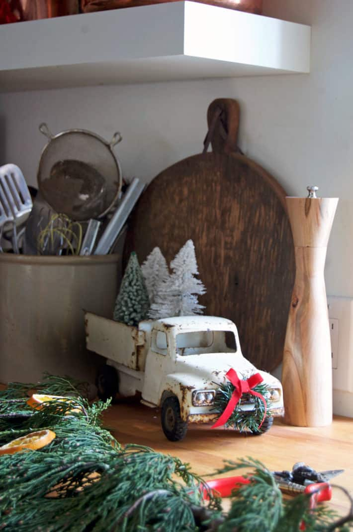 Vintage white, metal rusted toy truck with miniature wreath and red bow on the grill with garland in foreground.