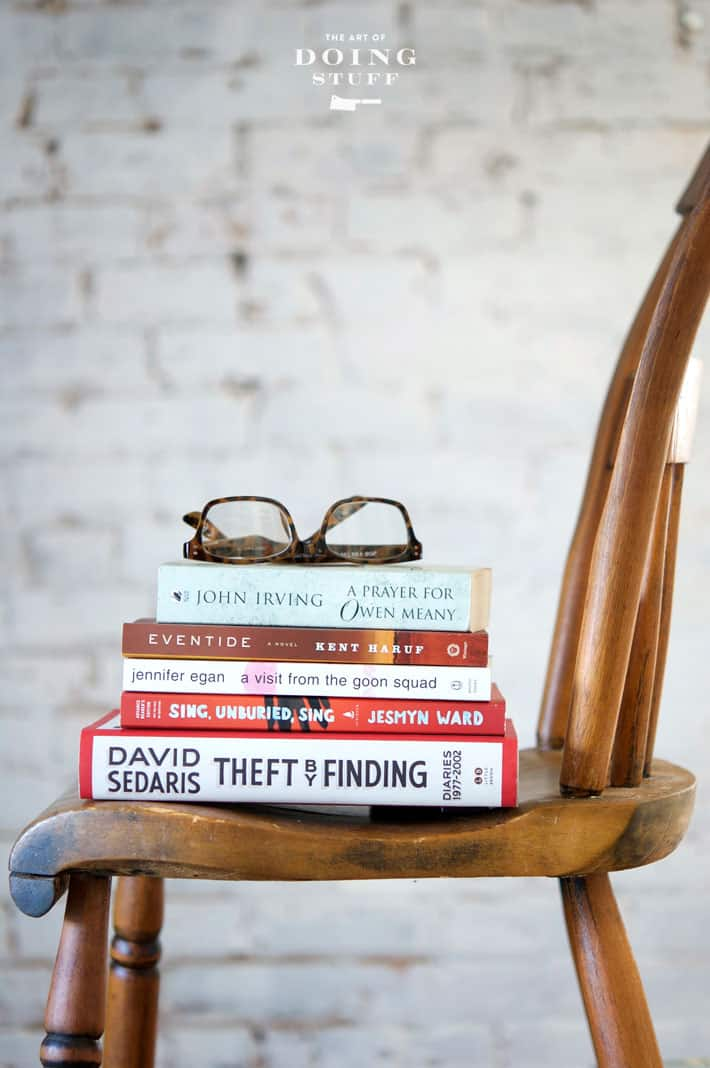 Side shot of an antique pine chair in front of a white brick wall. 5 books stacked on the chair seat topped with a pair of reading glasses.