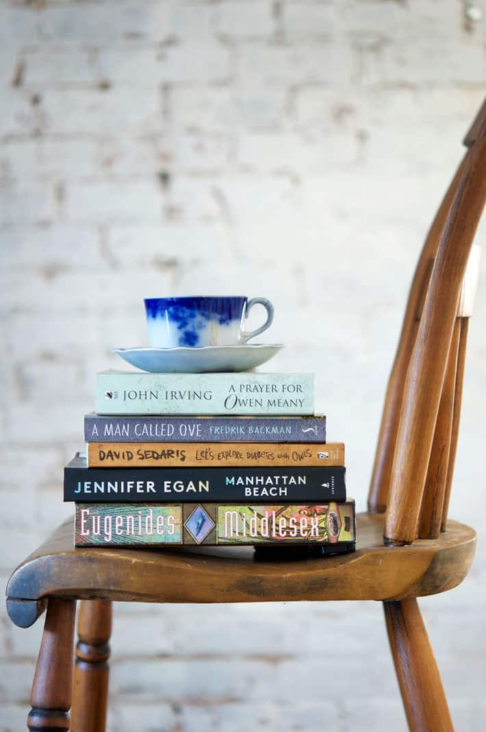 Side shot of an antique chair with a stack of books on it, topped with a flow blue tea cup.