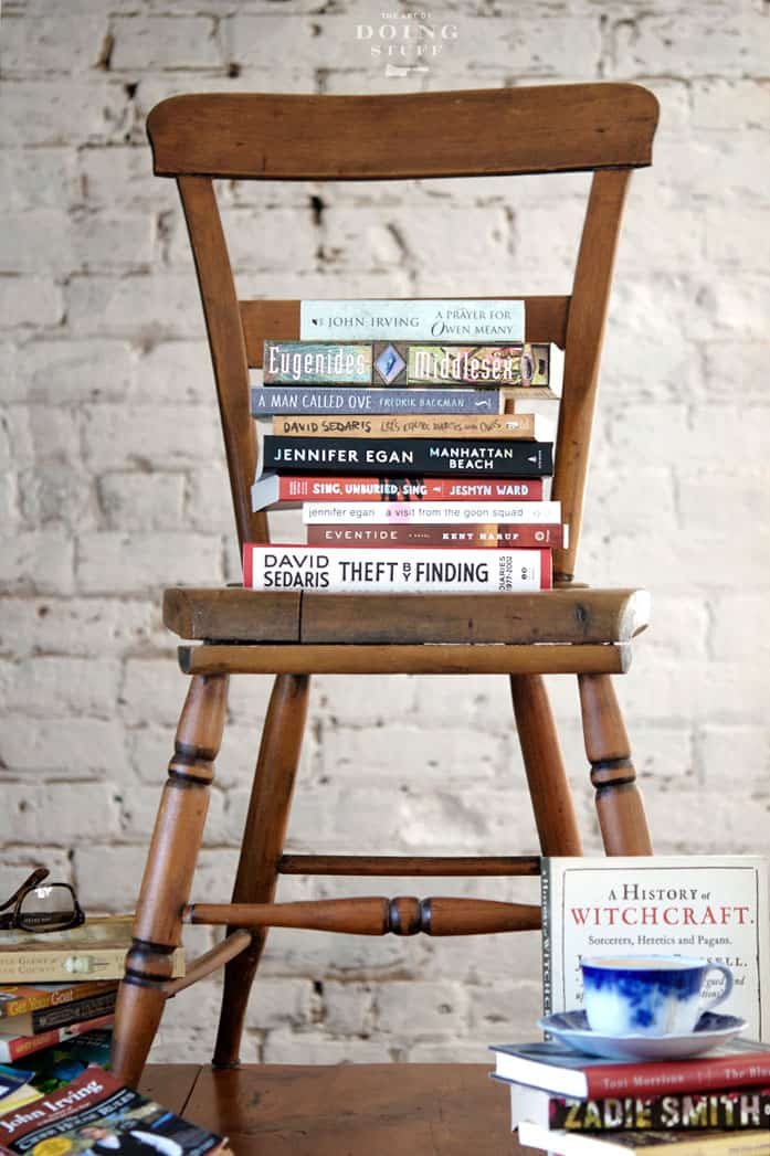 Antique pine kitchen chair with a stack of books on it and around it in front of a white brick wall.
