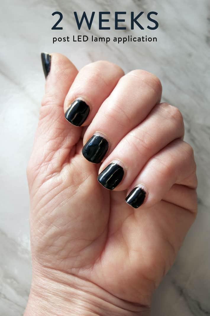Shot of hand with black polish 2 weeks after using LED nail lamp.