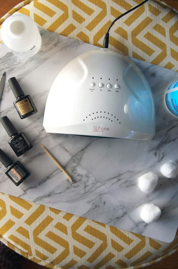 Overhead shot of an at home LED Nail lamp surrounded by polish, cotton balls and orange stick.