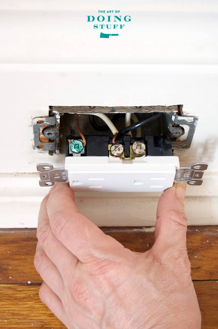 Gently pushing new electrical outlet into electrical box in white baseboard.