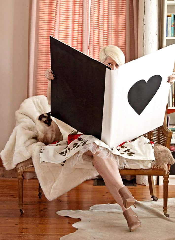 Woman on antique settee holding open a Valentine's card so big it covers most of her body with a Siamese cat beside her.