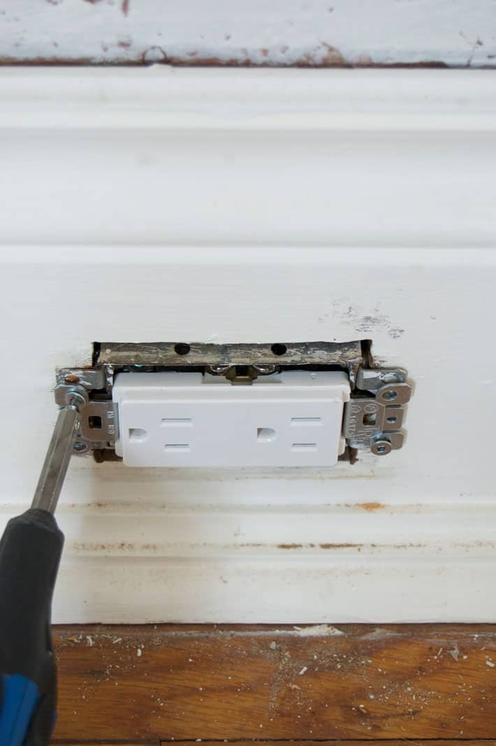 Screwing new white electrical outlet into white, wide baseboard.