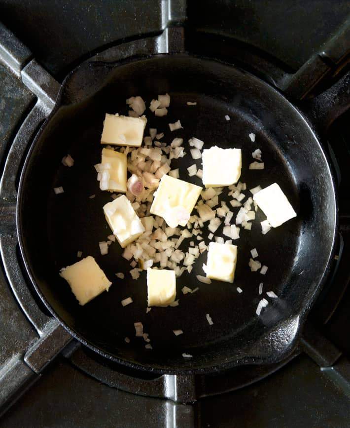 Cast iron pan on stove with chunks of butter and chopped shallot.