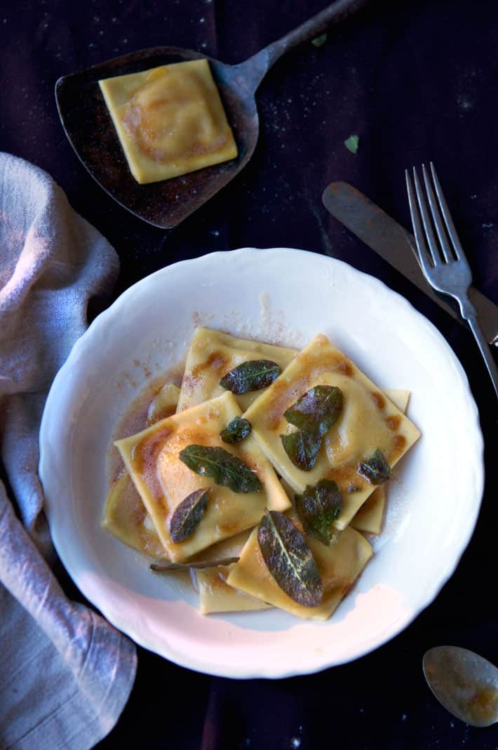 Homemade ravioli with sage leaves on ironstone plate with linen napkin.