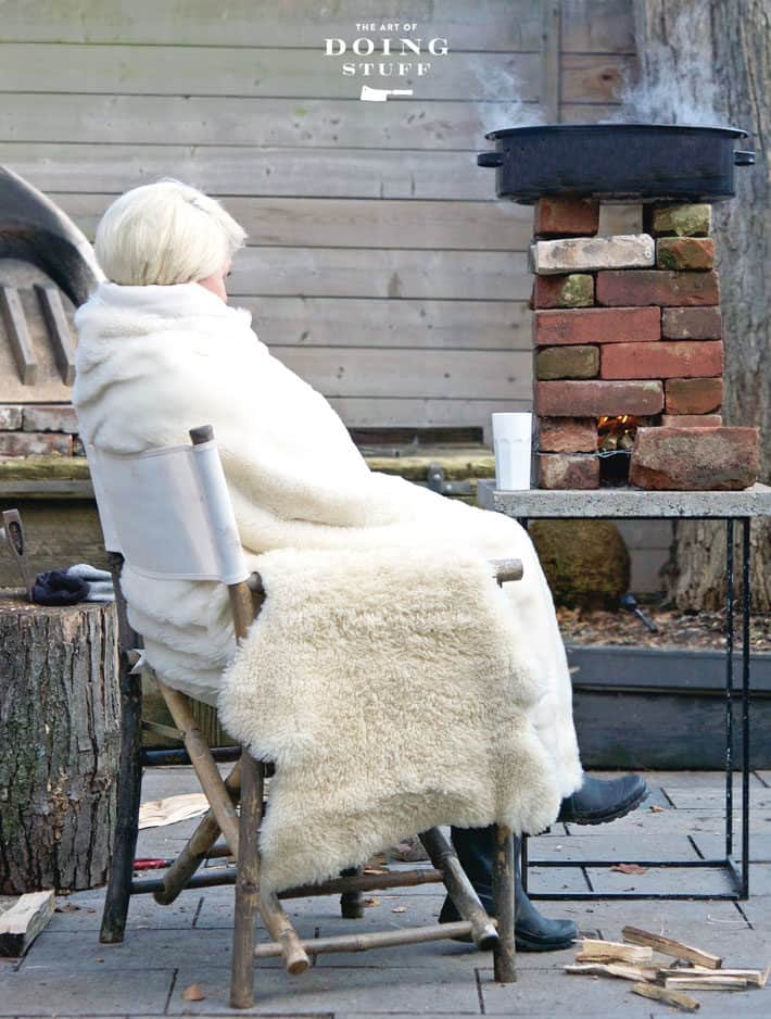 Karen Bertelsen bundled up in blankets sitting in a chair outside beside a rocket stove boiling maple syrup.