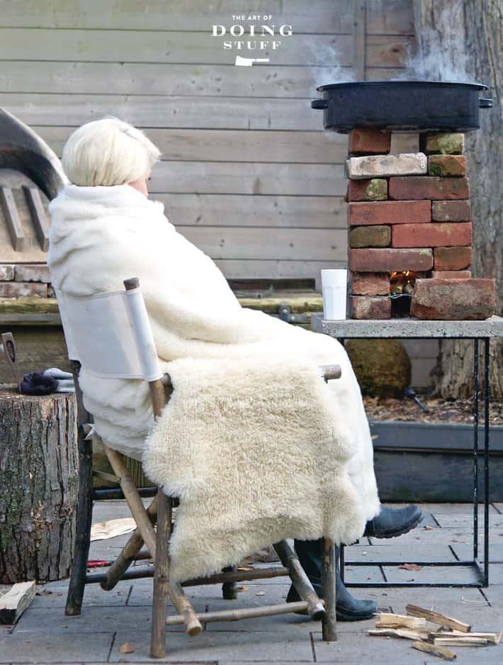 Karen Bertelsen sits outside bundled in blankets beside a brick rocket stove boiling maple syrup sap.