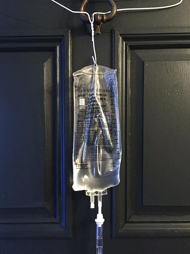 A subq fluids bag for cats hanging higher than the cat on a wire coat hanger on a black door.