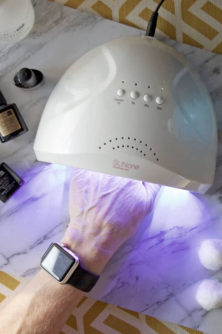Overhead shot of hand curing nails in LED nail light.