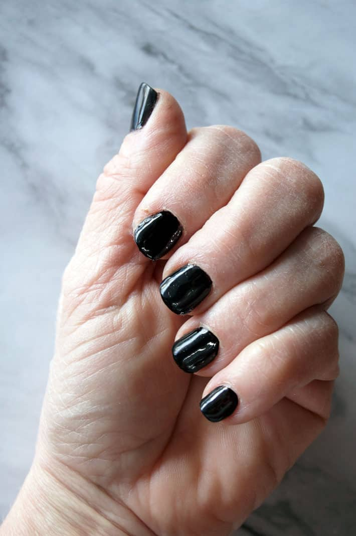 Close up shot of fingernails painted black. Hand is dry.
