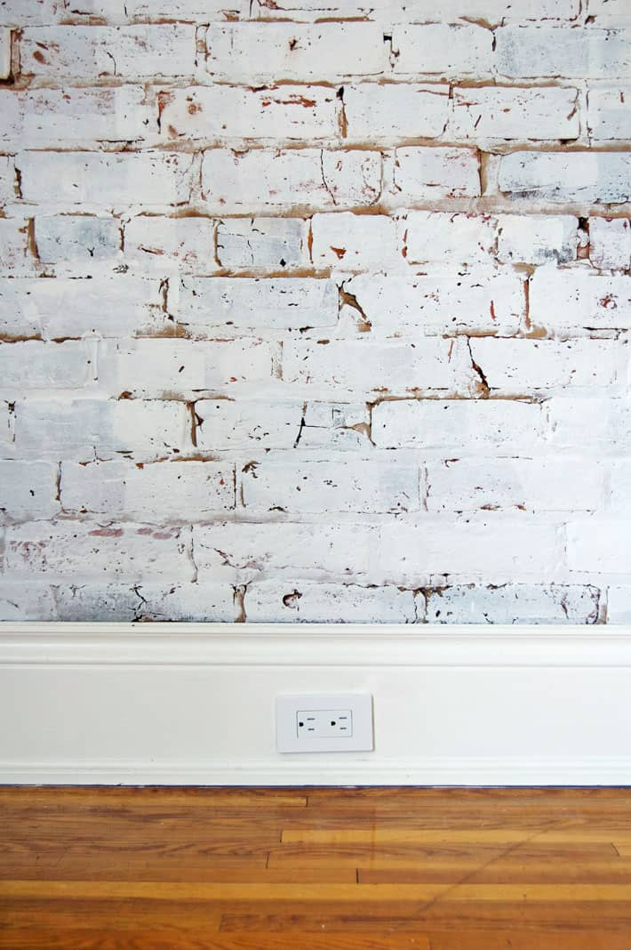White painted brick wall with wide white baseboard and new white electrical outlet.
