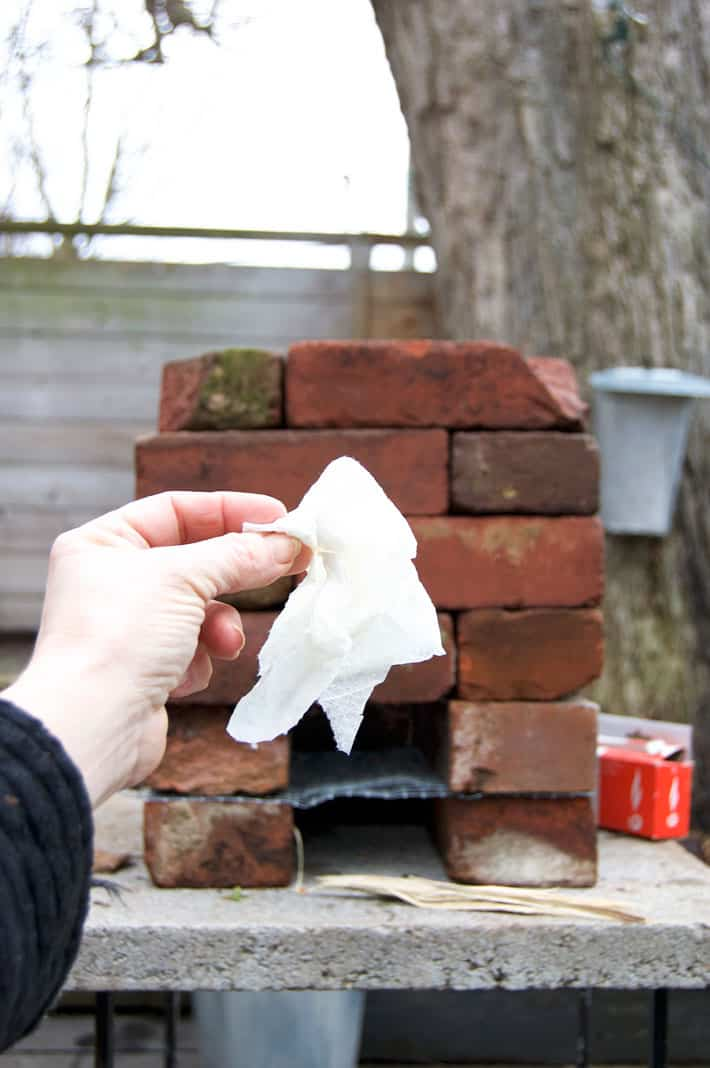 A vegetable oil soaked paper towel held up in front of a brick rocket stove outside.