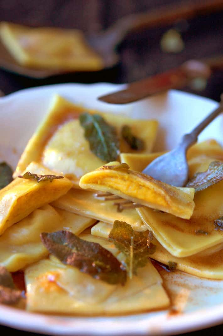 Homemade pumpkin ravioli on fork, with view of filling.
