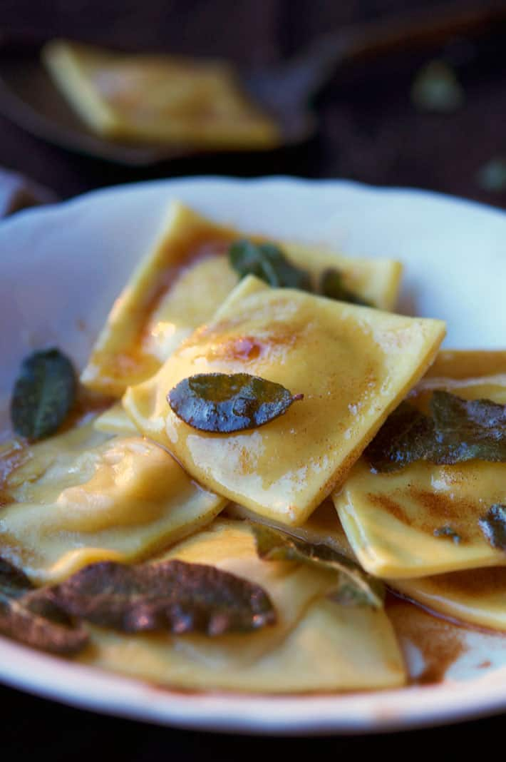 Homemade pumpkin ravioli in ironstone bowl with fried sage leaves and drizzled with browned butter.