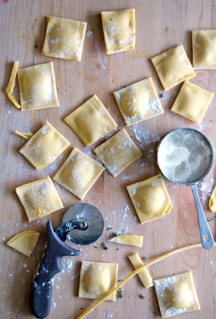 Flour dusted homemade ravioli scattered on butcher block countertop.