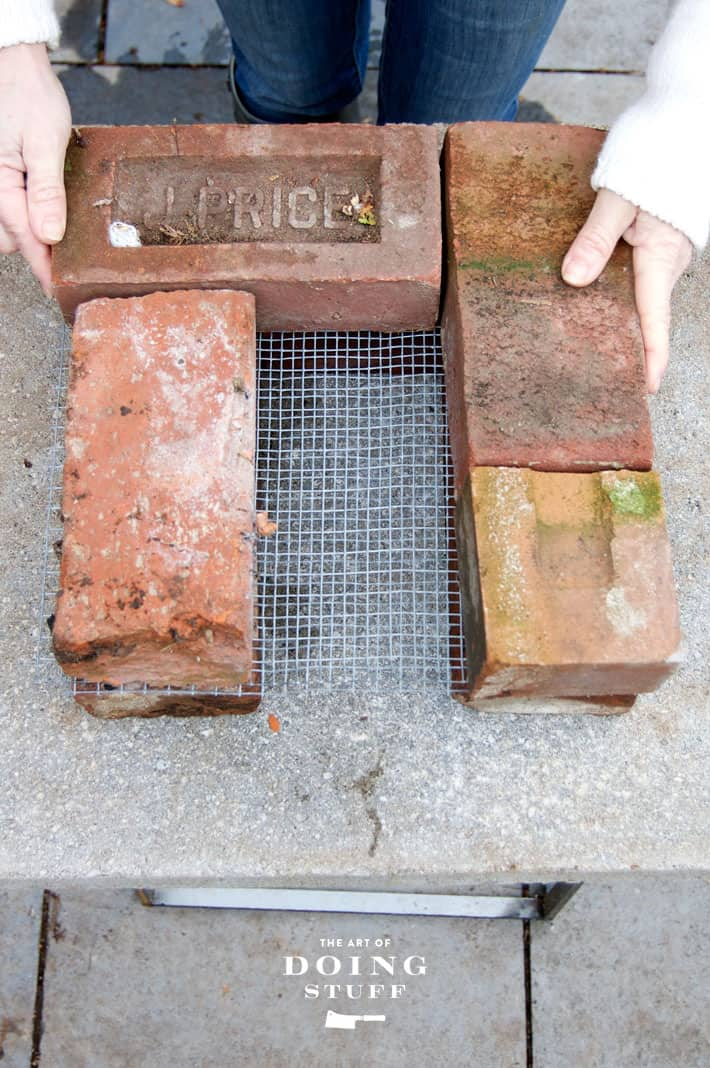 Setting antique bricks on top of hardware cloth for the base of a rocket stove.