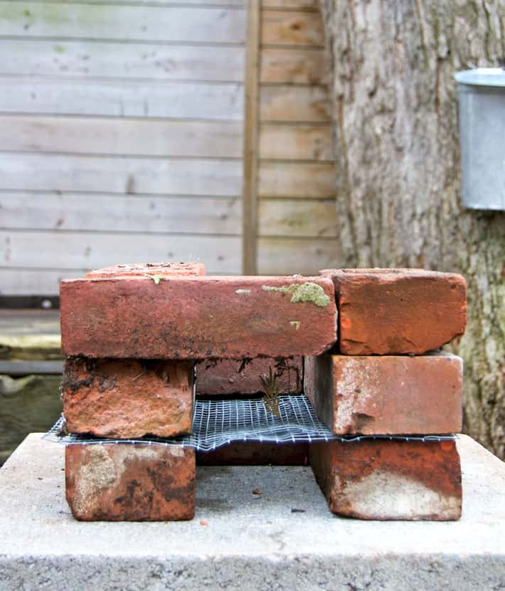 A rocket stove at the beginning of assembly with 3 layers of bricks.