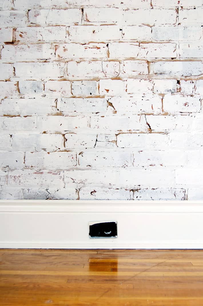 White brick wall with wide white baseboard, dark brown, paint splattered old electrical outlet in the middle of the baseboard.