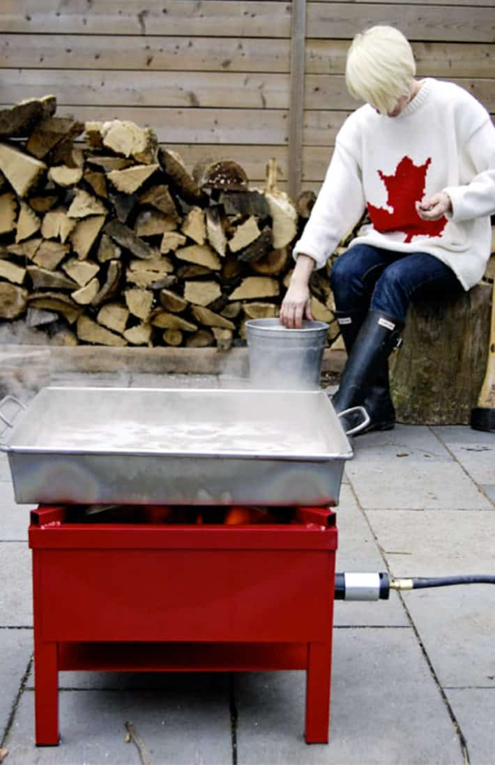 Karen Bertelsen in a sweater with a red maple leaf on it in her backyard with an evaporation pan of sap reducing on a propane burner.