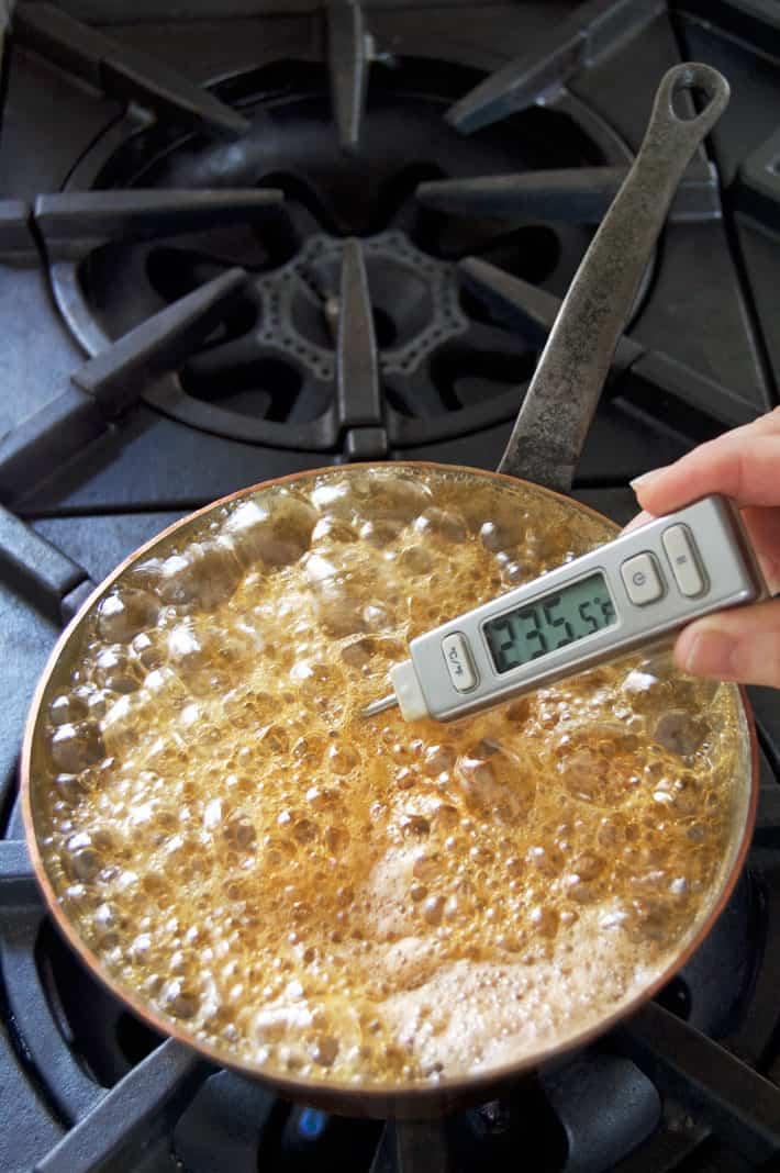 Boiling maple syrup on stove with thermometer in it reading 235.5 degrees F.