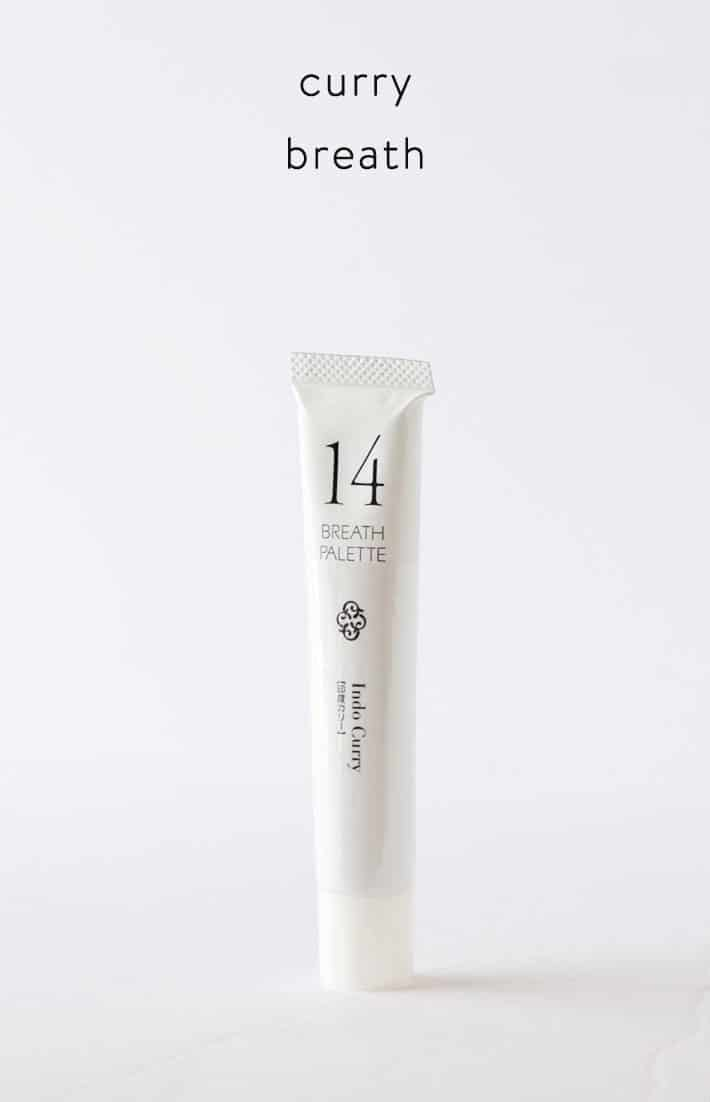 White, thin elegant tube of toothpaste with fine black letter, Indo Curry toothpaste.