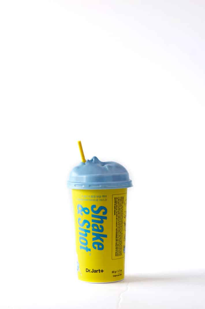 Yellow and baby blue paper cup with a plastic lid and straw. The plastic lid is in the shape of a face. Weird.