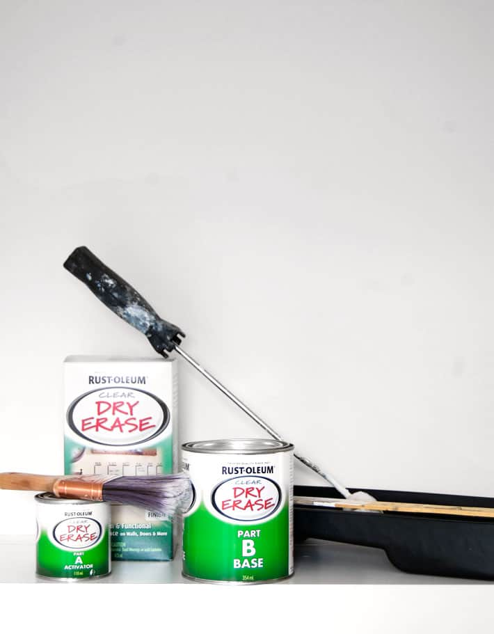 Materials needed for painting a dry erase wall laid out including Rust-oleum's dry erase paint and paint rollers.