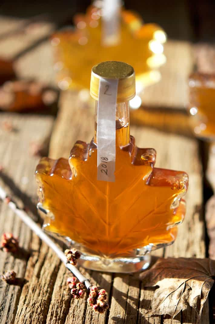 Light shining through bottle of amber maple syrup.