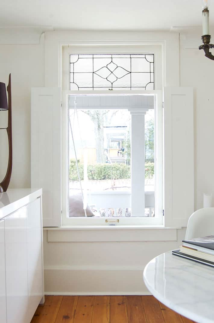 White shaker style interior shutters in heritage home.